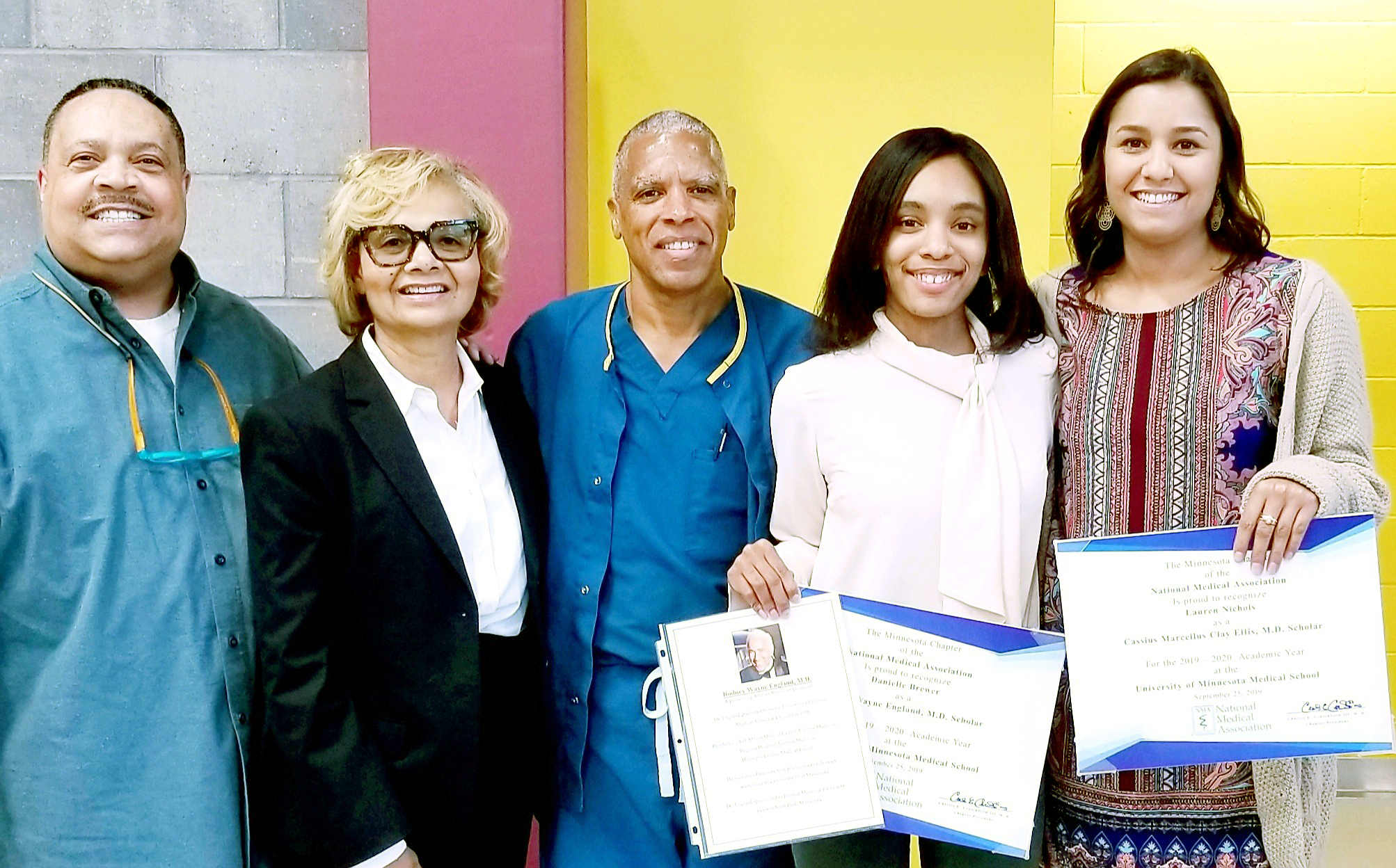 Five people standing together, including two Medical School students with awards.
