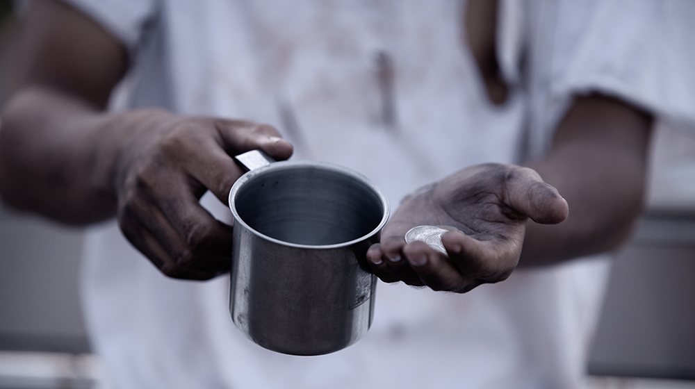 A Black man's hands holding a cup and coins.
