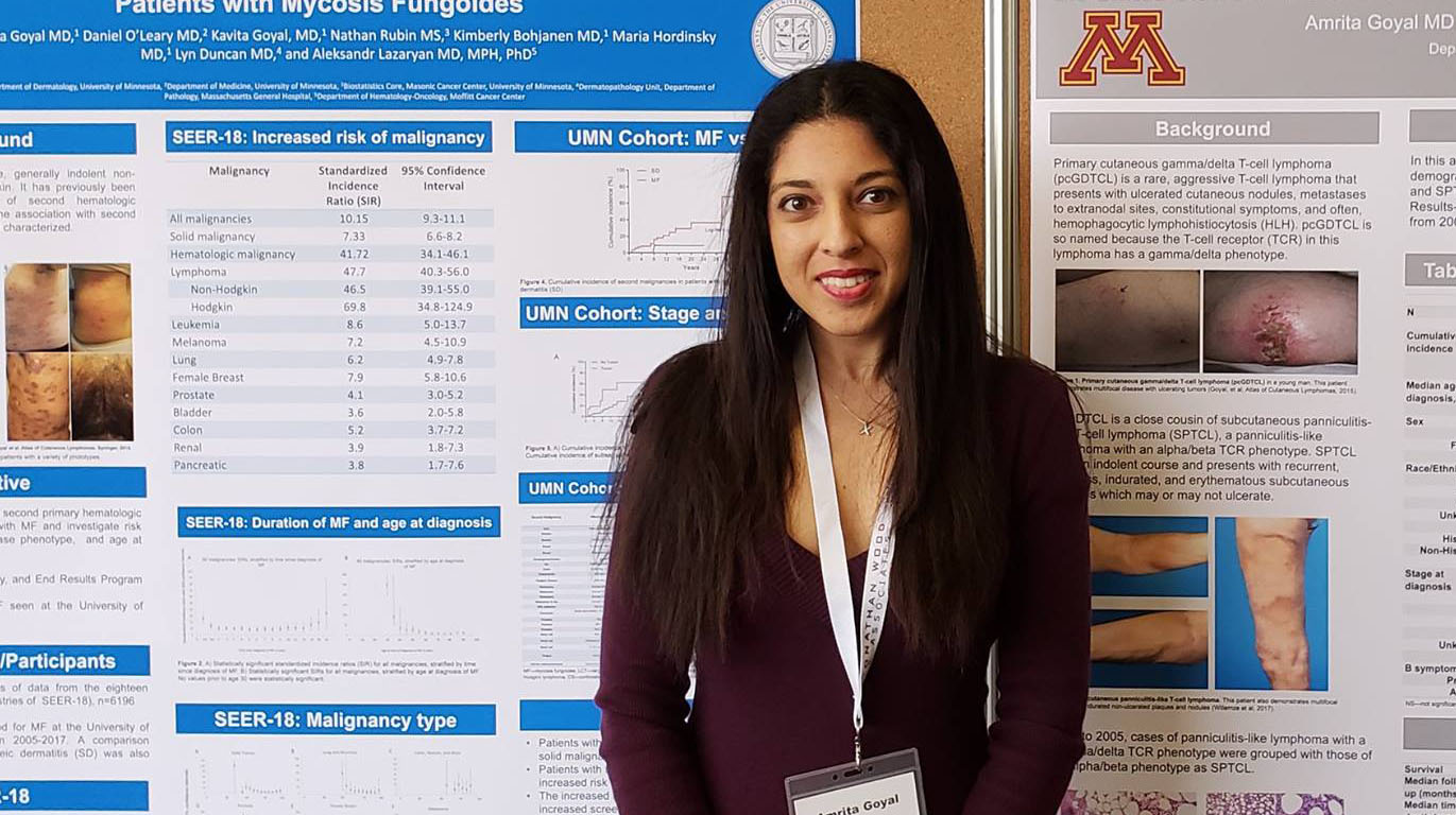 Dermatology trainee standing by research poster