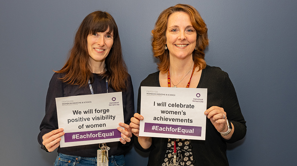 two women holding up each for equal signs