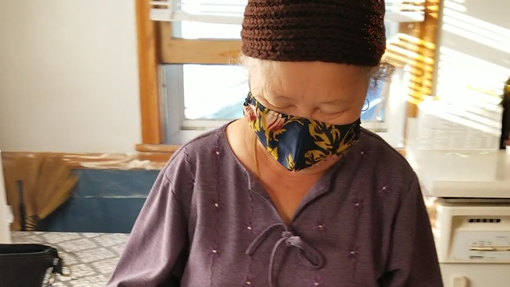 An older woman wearing a mask.