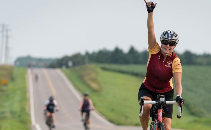 Woman on a bike riding down a rural road