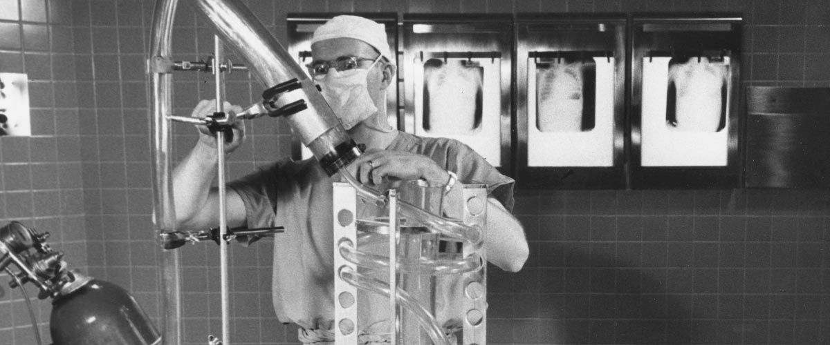 Historic photo of Richard DeWall, M.D., with his Lillehei-DeWall Bubble Oxygenator