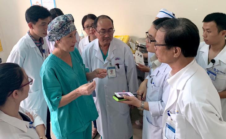 People standing around listening to a surgeon talk.