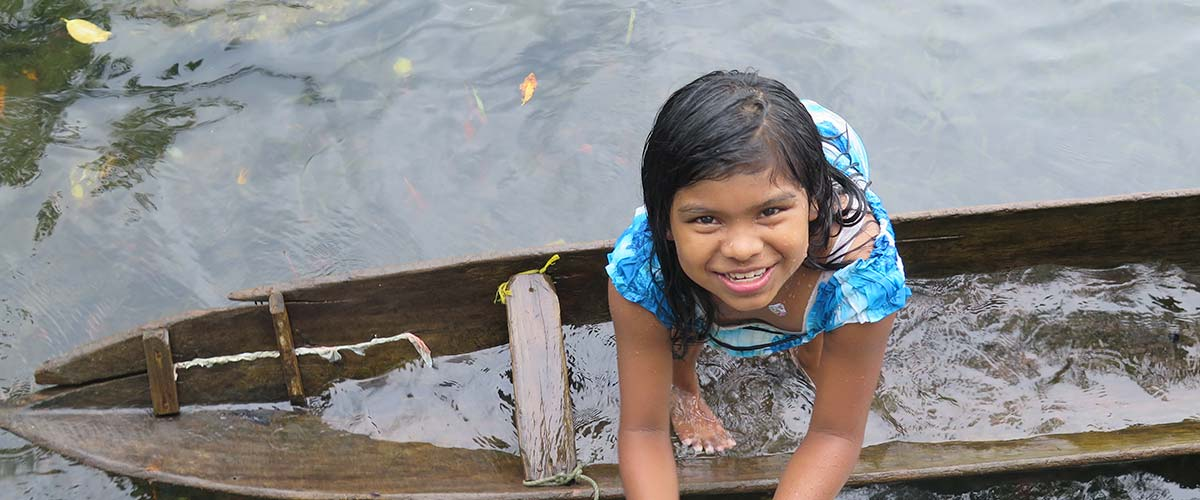 Girl looking up at camera while standing in a boat