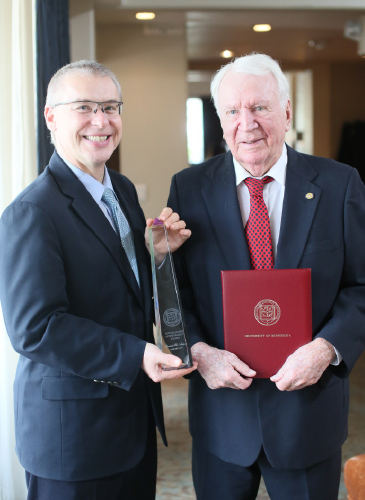 Jakub Tolar, M.D., Ph.D., the Medical School's executive vice dean, presents 97-year-old  Forrest Adams, M.D., with his award.