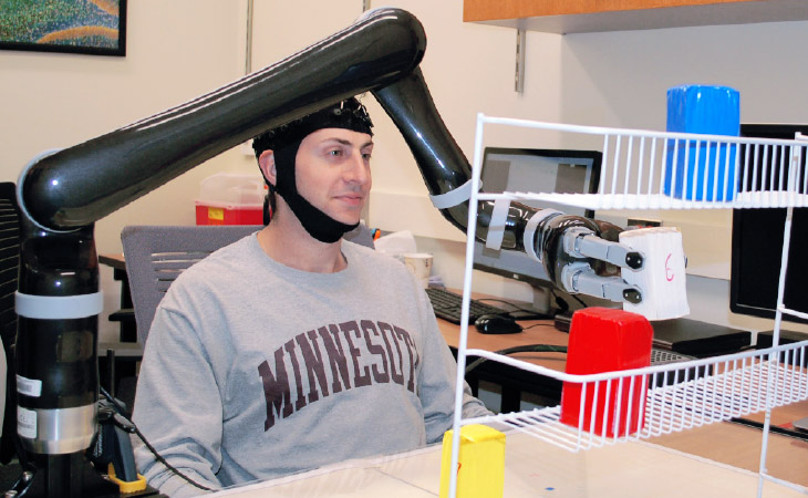 Image of man controlling robotic arm with his mind.