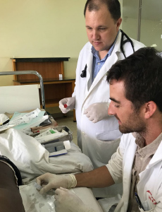 Rhein supervises visiting U of M internal medicine resident Alex Zanotto, M.D., while he performs a lumbar puncture on a patient with meningitis.