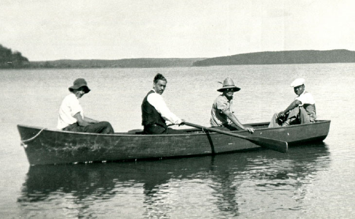 Historic photo of four men in a canoe