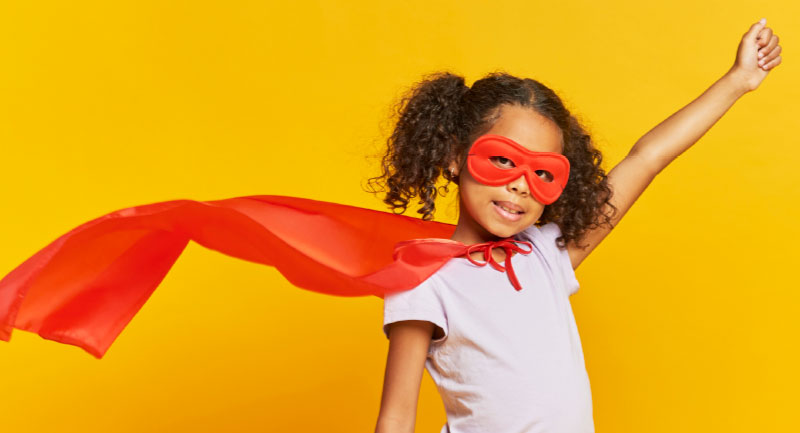 Child wearing a cape against a yellow background