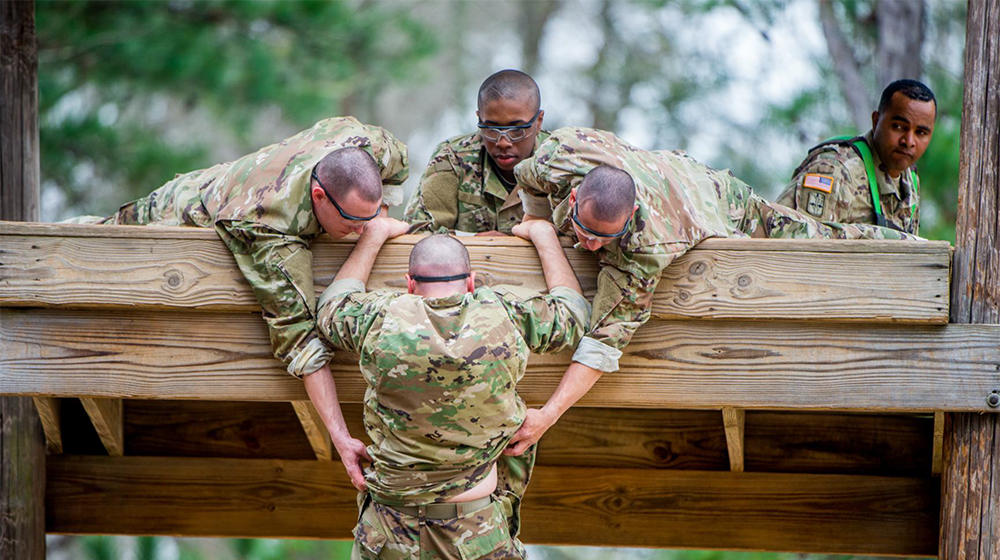 Soldiers helping another soldier up a wall.