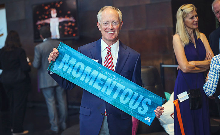 Tom Olson holding sign with Momentous spelled out
