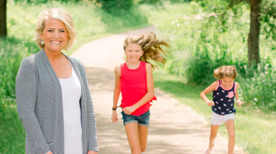 A woman looking at the camera with her two daughters running toward her