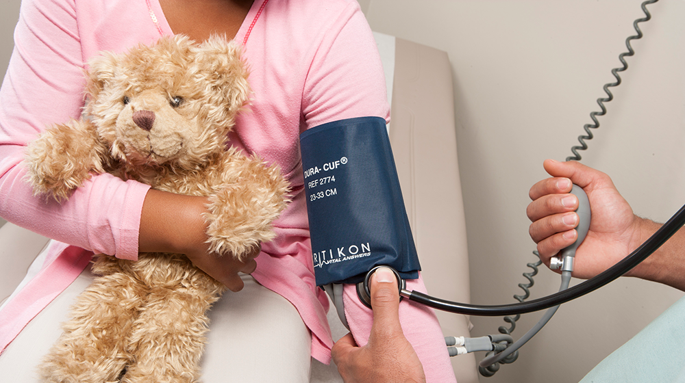 A young girl holding a teddy bear, getting her blood pressure taken.