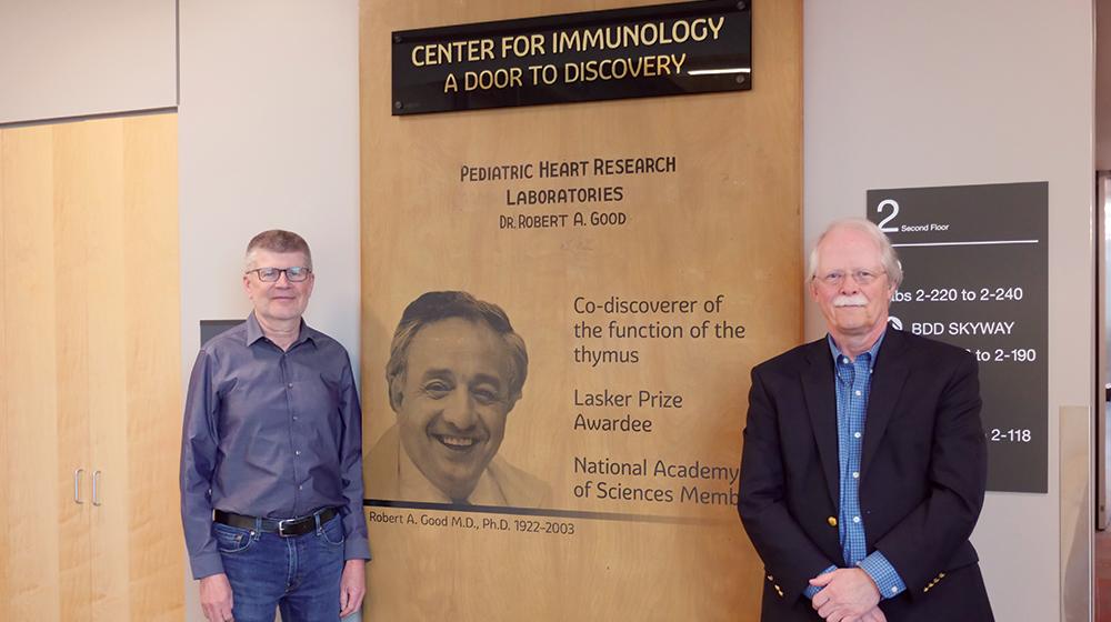 Tucker LeBien and Marc Jenkins standing in front of Robert Good's Lab Door in UMN Center For Immunology