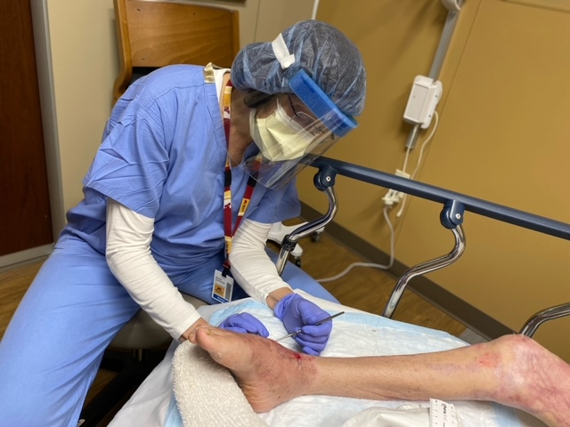 Sandra Rosenberg working on a patients wound