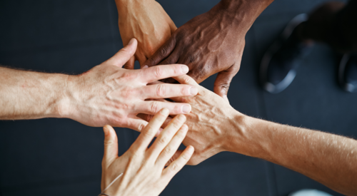 Hands joining together for article titled, Faculty-Student Partnerships Lead to Socially-Responsive Medical Education
