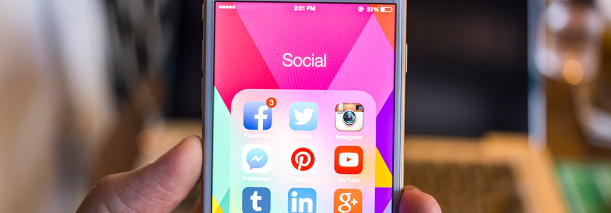 A hand holding a phone with social icons on the screen.