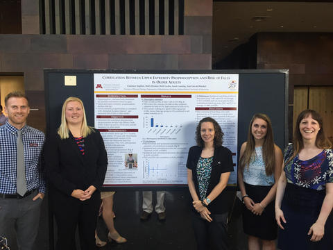 Physical therapy students presenting research poster.