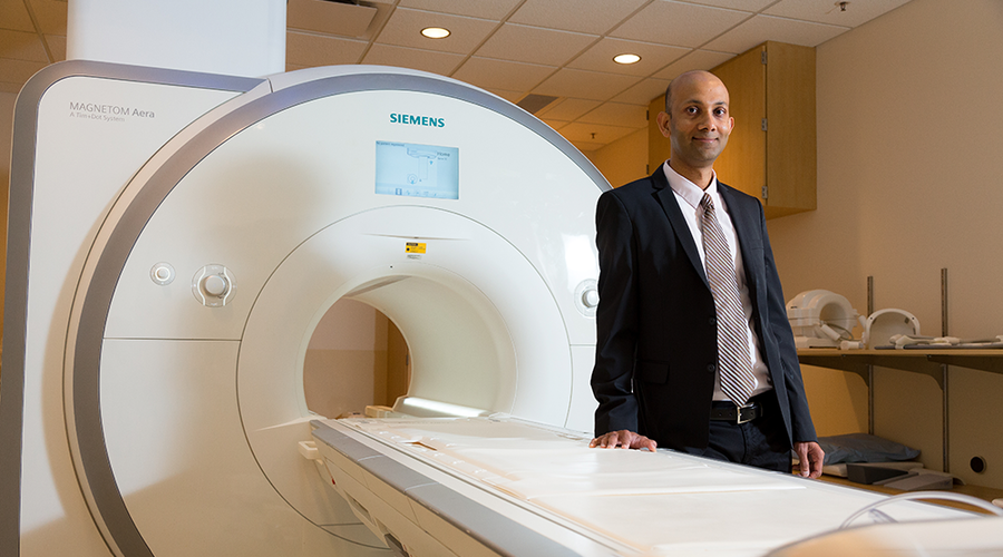 Dr. Chetan Shenoy standing in front of an MRI machine.