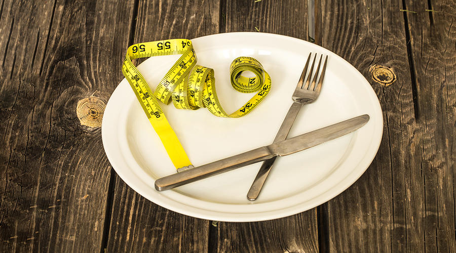 A plate on a wooden table with a fork and measurement tape on the plate.
