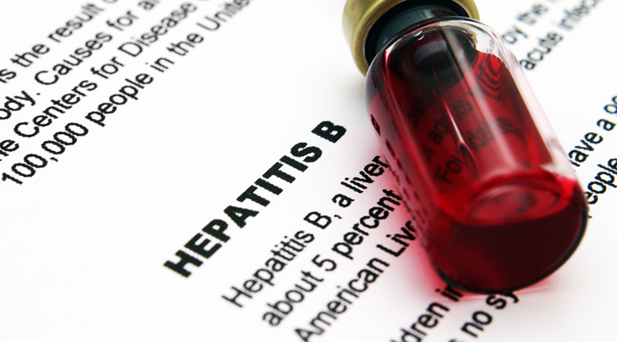 A blood sample sitting on top of a piece of paper with information about Hepatitis B
