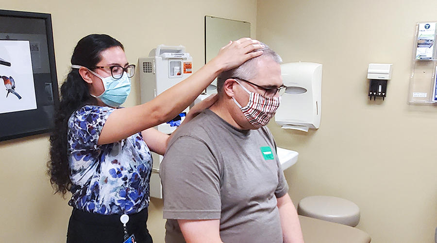 A female student checking the neck of a male patient.