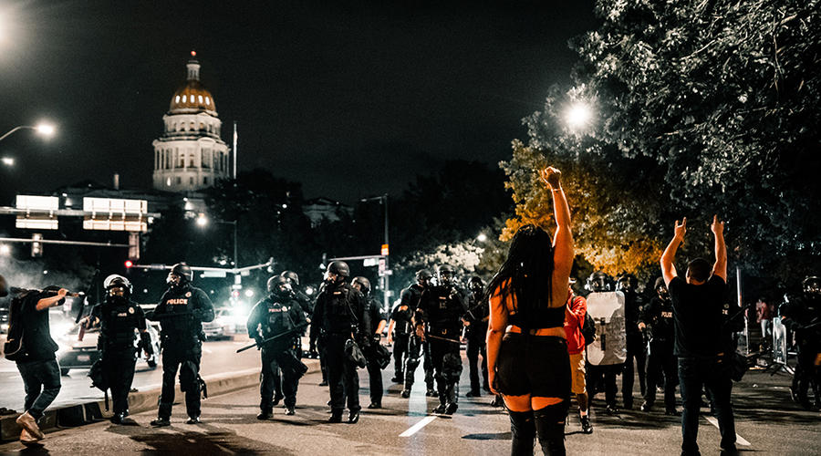 Protestors clashing non-violently with a line of police in riot gear.