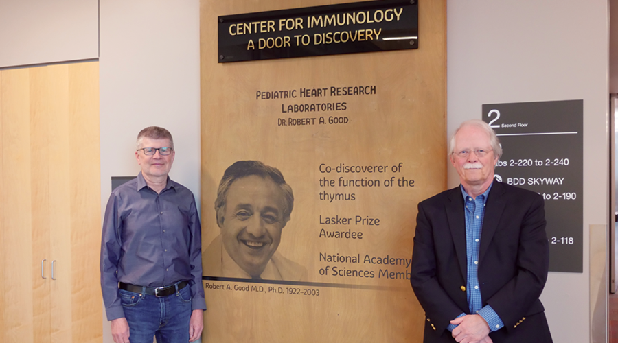 Tucker LeBien and Marc Jenkins standing in front of Robert Good's Lab Door in UMN Center For Immunology