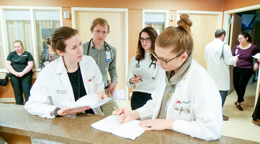 Two medical students watching two physicians with clipboards.