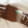 A close-up of a Black patient's hand with tape, hospital bands, and IVs.