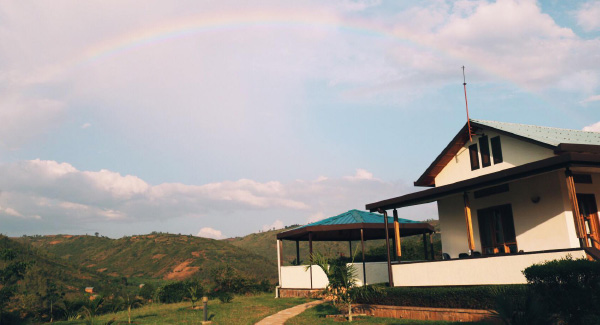House in the mountains with a rainbow in the sky