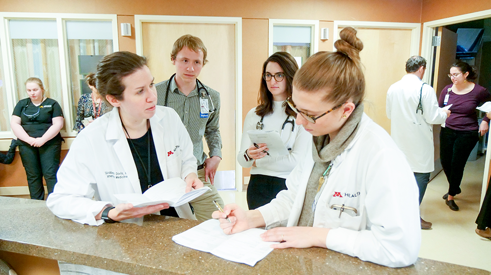 Two students observing two physicians in a hospital ward.