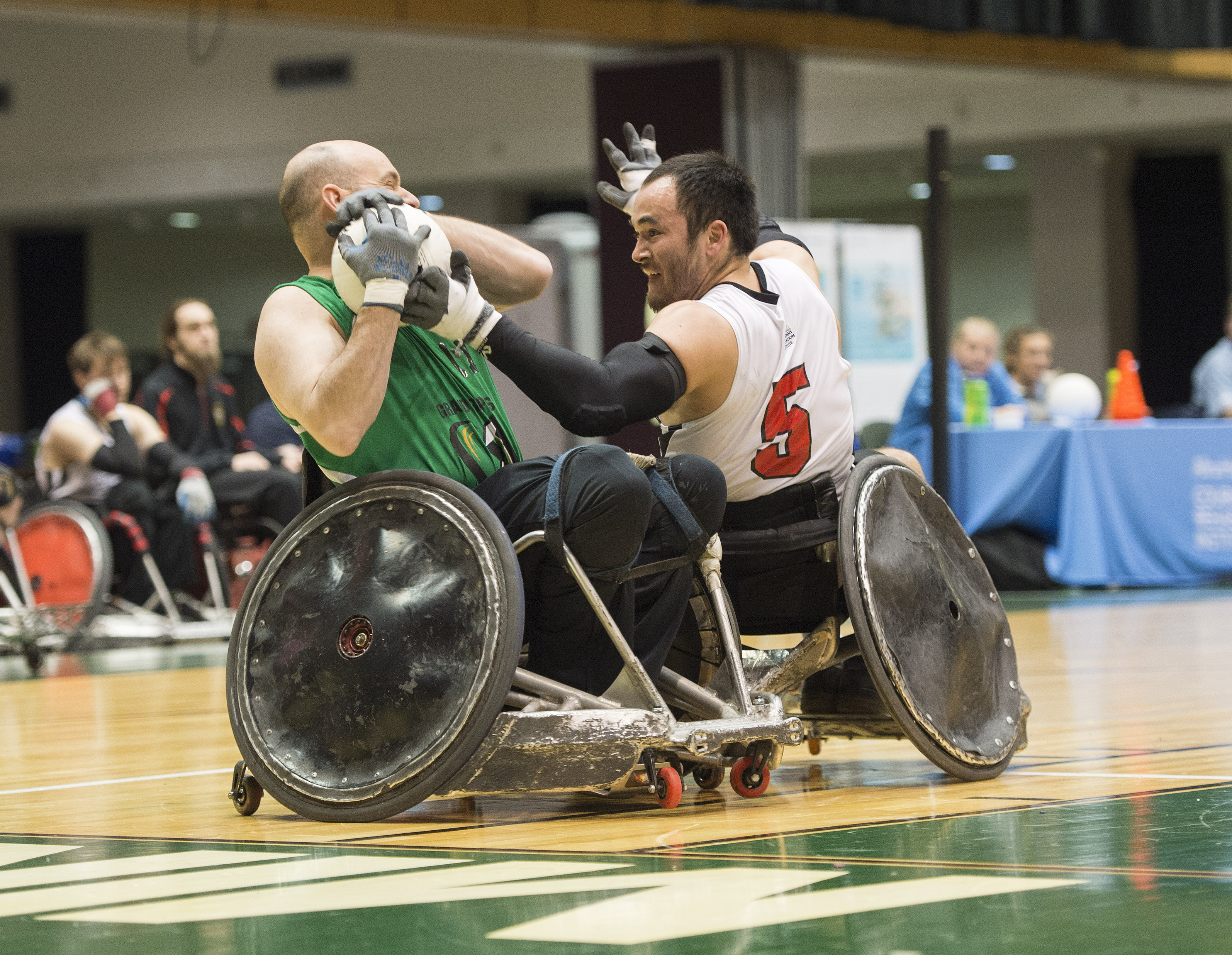 Two individuals playing wheelchair rugby.